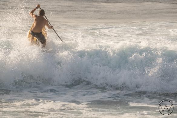 Kody Kerbox paddling through the surf